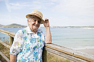 Happy senior woman with straw hat standing on boardwalk - RAEF001421