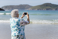 Back view of senior woman on the beach taking picture with smartphone - RAEF001427