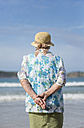 Back view of senior woman wearing straw hat on the beach looking at distance - RAEF001430