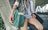 Woman holding green shoulder bag, partial view - DAPF000283