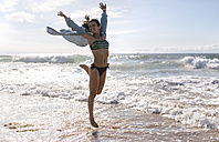 Spain, Asturias, beautiful young woman jumping on the beach - MGOF002202