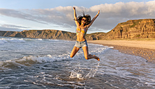 Spain, Asturias, beautiful young woman jumping on the beach - MGOF002232