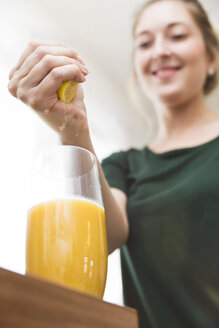 Woman squeezing lemon juice into glass of homemade smoothie - MIDF000784