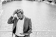 Businessman standing on bridge holding tablet - KNSF000382
