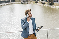 Businessman standing on bridge with tablet on cell phone - KNSF000385