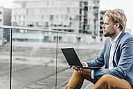Businessman sitting on bridge using laptop - KNSF000391