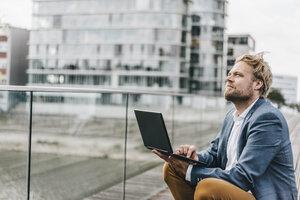 Businessman sitting on bridge using laptop looking up - KNSF000394