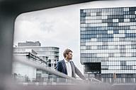 Businessman standing on bridge - KNSF000400