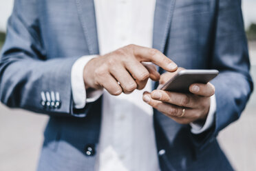 Close-up of businessman using cell phone - KNSF000406