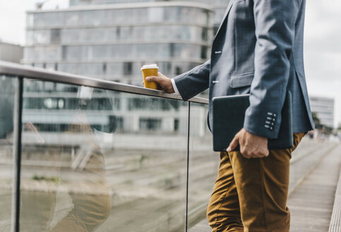 Businessman standing on bridge with coffee and tablet - KNSF000418