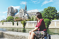 France, Paris, woman sitting on the bank of the Seine river in front of Notre-Dame de Paris - GEMF000971