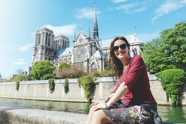 France, Paris, smiling woman sitting on the bank of the Seine river in front of Notre-Dame de Paris - GEMF000977