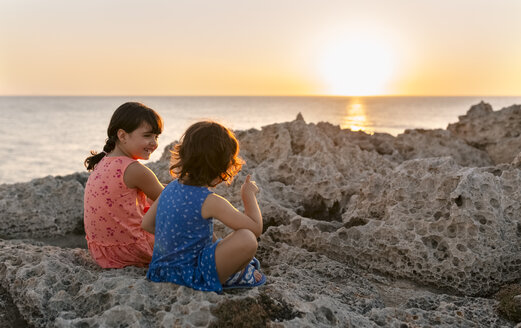 Back view of two little sisters sitting at rocky coast by sunset - MGOF002251