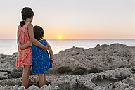Back view of two little sisters standing arm in arm at rocky coast watching sunset - MGOF002254