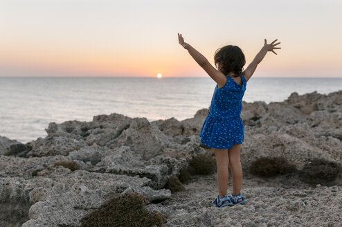 Back view of little girl with raised arms at rocky coast by sunset - MGOF002257