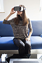 Woman sitting on couch wearing virtual reality glasses - NDF000588