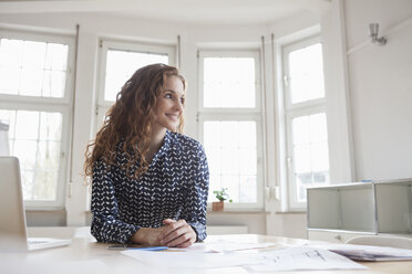 Smiling woman at desk in office - RBF005001