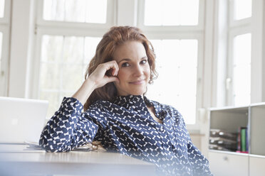 Portrait of smiling woman at desk in office - RBF005022
