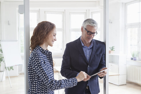 Businessman and woman in office with tablet - RBF005028