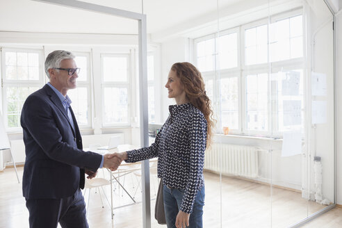 Businessman and woman shaking hands in bright office - RBF005031