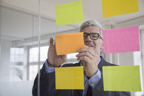 Businessman in office attaching adhesive notes at glass pane - RBF005037