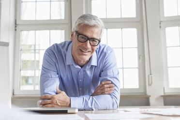 Portrait of confident mature businessman at office desk - RBF005049