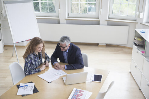 Businessman and woman sitting at boardroom table looking at documents - RBF005064