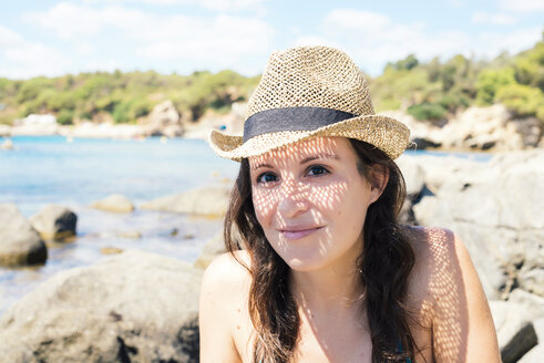 Portrait of smiling woman wearing straw hat on the beach - GEMF000980