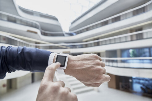 Businessman touching smartwatch in office building - FMKF002890