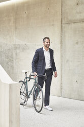 Businesssman pushing bicycle along concrete wall - FMKF002914