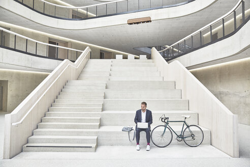 Businesssman on stairs using laptop next to bicycle - FMKF002929