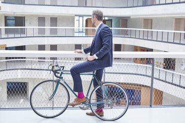 Businesssman with bicycle in modern office building - FMKF002941