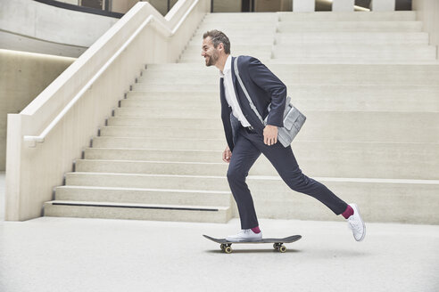 Businesssman riding skateboard at staircase - FMKF002944