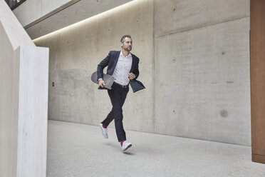 Businesssman running with skateboard along concrete wall - FMKF002947