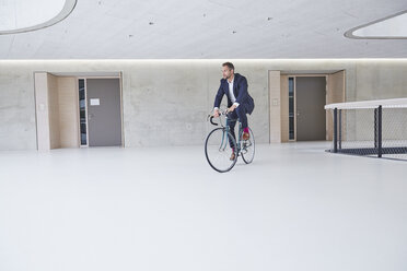 Businesssman riding bicycle in office building - FMKF002965