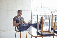 Man using tablet at table with chairs on it - FMKF002968