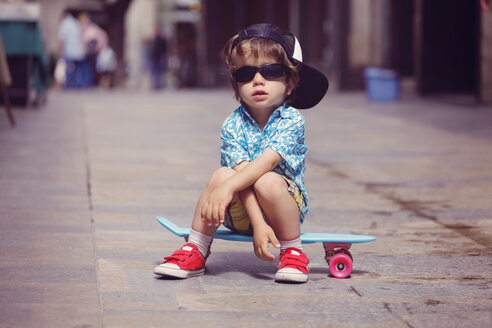 Portrait of little boy sitting on  skateboard wearing oversized sunglasses and basecap - XCF000097