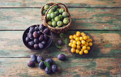 Baskets of plums, mirabelles and greengages on wood - PPXF000026