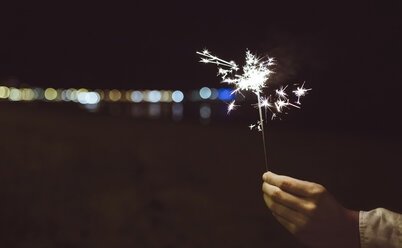 Man's hand holding sparkler on the beach at night - DAPF000297