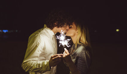 Kissing young couple holding sparklers on the beach at night - DAPF000300