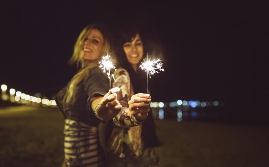Two happy friends holding sparklers on the beach at night - DAPF000303