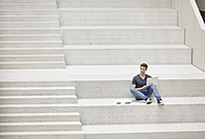 Young man sitting on stairs using laptop - FMKF002974