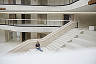Young man sitting on stairs in office building using laptop - FMKF002989