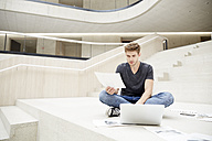 Young man sitting on floor with laptop and papers - FMKF002998