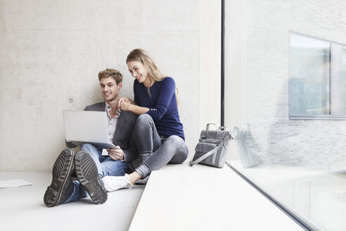 Smiling young couple sitting at concrete wall sharing laptop - FMKF003004