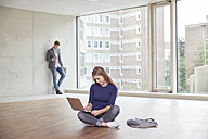 Young woman using laptop in empty room with man in background - FMKF003010
