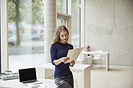 Young woman looking at documents - FMKF003013