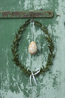 Painted Easter egg and box tree wreath hanging in front of green door - ASF005990
