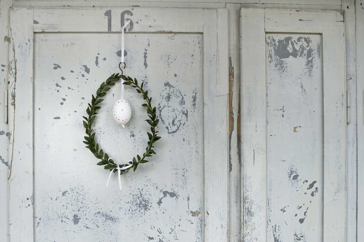 Easter egg and box tree wreath hanging in front of wooden door - ASF005996 - Achim Sass/Westend61