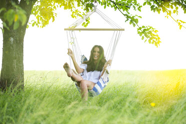 Happy woman relaxing in a hanging chair under a tree - MAEF011944